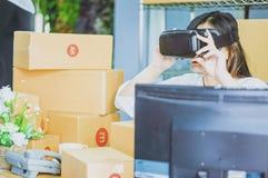 亚裔妇女开始小企业主,使用vr与包装的产品的纸板箱沟通,在家 库存图片