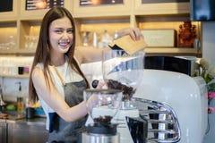 亚裔妇女微笑和使用咖啡机的Barista在咖啡馆反的职业妇女小企业主食物和饮料 库存照片
