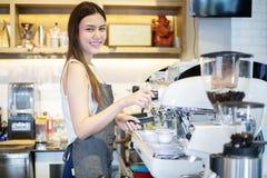 亚裔妇女微笑和使用咖啡机的Barista在咖啡馆反的职业妇女小企业主食物和饮料 图库摄影
