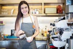亚裔妇女微笑和使用咖啡机的Barista在咖啡馆反的职业妇女小企业主食物和饮料 免版税图库摄影