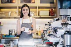 亚裔妇女微笑和使用咖啡机的Barista在咖啡馆反的职业妇女小企业主食物和饮料 免版税库存照片