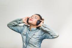 亚裔妇女愉快地使用耳机 免版税库存图片