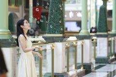亚裔妇女愉快地起来她的看肥皂泡的顶头微笑 图库摄影