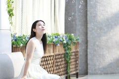 亚裔妇女愉快地起来她的看肥皂泡的顶头微笑 免版税库存照片