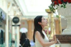 亚裔妇女愉快地起来她的看花的顶头微笑 库存照片