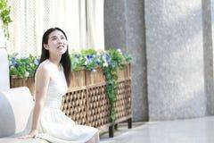 亚裔妇女愉快地起来她顶头微笑看 库存照片