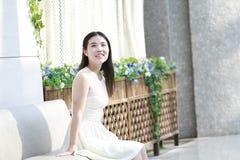 亚裔妇女愉快地起来她顶头微笑看 图库摄影