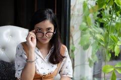 亚裔妇女拿着玻璃并且微笑着在咖啡店  免版税库存照片