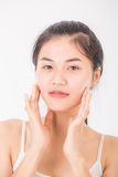 亚裔妇女按摩她的面孔并且应用奶油色化妆用品 库存图片