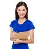 亚裔妇女摘记关于clipoard的笔记 库存照片