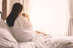亚裔妇女放松在酒店房间的,饮用的早晨咖啡 免版税库存照片