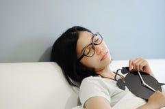 亚裔妇女是与闹钟的睡眠在床上 免版税库存图片