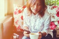 亚裔妇女是听的音乐 库存图片