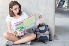 亚裔妇女是坐和拿着城市旅行的一张地图 库存照片