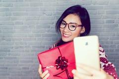 亚裔妇女是愉快接受礼物 图库摄影