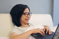 亚裔妇女是愉快的她的在床上的膝上型计算机 免版税图库摄影