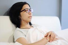 亚裔妇女是睡眠和在她的床上 免版税库存图片