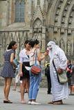 亚裔妇女显示照片给一个智能手机的一位街道艺术家在巴塞罗那街道上  库存照片