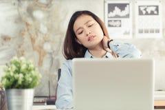 亚裔妇女有从工作的脖子痛在办公室 免版税库存图片