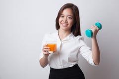 年轻亚裔妇女用哑铃饮料橙汁 库存图片