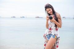 亚裔妇女由数码相机享用作为照片在海滩 唯一和偏僻的妇女概念 幸福和生活方式概念 beauvoir 免版税库存图片