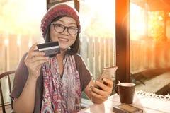 亚裔妇女的幸福情感有信用卡手中用途的fo 免版税库存图片