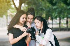 亚裔妇女编组看照相机` s显示器检查的游人 免版税图库摄影