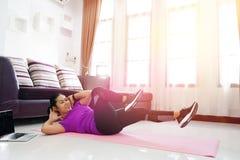 亚裔妇女行使在家做胃肠吸收锻炼,与u 免版税库存图片