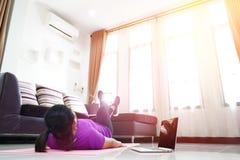 亚裔妇女行使在家做腿剪刀胃肠吸收锻炼 免版税库存图片