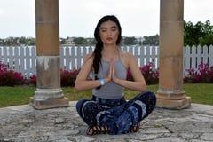 年轻亚裔妇女触击在天堂海岛,巴哈马上的一个冥想的姿势 库存照片