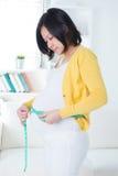 亚裔妇女评定她的胃 免版税图库摄影