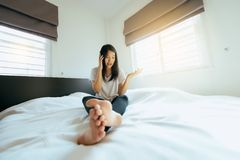 亚裔妇女谈话在移动电话在感到的卧室严肃 免版税库存照片