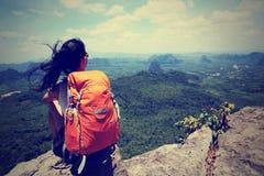 亚裔妇女远足者享受在山峰峭壁的看法 免版税图库摄影