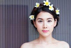 亚裔妇女面对美丽有在头的花 免版税库存照片