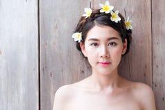 亚裔妇女面对美丽有在头的花 库存图片