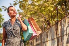 亚裔妇女顾客是购物和拿着看斜向一边在左边在右边的和拷贝空间的五颜六色的购物袋 免版税库存图片