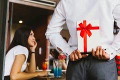 亚裔妇女预计从人接受惊奇礼物礼物盒作为偶尔的周年庆祝的一对浪漫夫妇 免版税库存图片