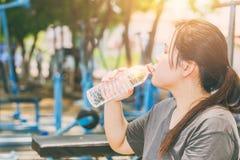 亚裔妇女饮用水在热的天 库存照片