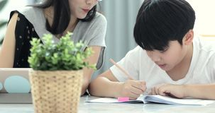 亚裔妈妈帮助她的儿子做家庭作业 股票视频