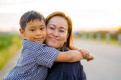 亚裔妈妈爱恋拥抱她的年轻儿子在与自然backg的日落 库存图片
