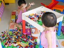 亚裔婴孩清扫她使用与她的妹的玩具 免版税库存照片
