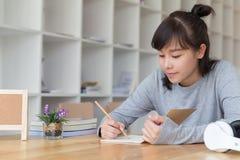 亚裔学习在学校的女孩女性少年 写n的学生 免版税库存图片