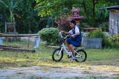 亚裔学生女孩佩带的校服,在l享用一辆自行车 库存照片