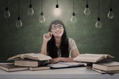亚裔学生有明亮的想法在电灯泡下 免版税库存图片