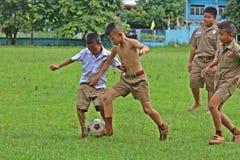 亚裔学生踢橄榄球 免版税库存图片
