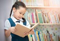 亚裔学生逗人喜爱的女孩阅读书在图书馆里 图库摄影