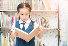 亚裔学生逗人喜爱的女孩阅读书在图书馆里 库存图片