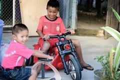 亚裔孩子在乡区对一个新的玩具满意 库存照片