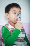 亚裔孩子拿着哮喘的治疗的一台面具蒸气吸入器 图库摄影