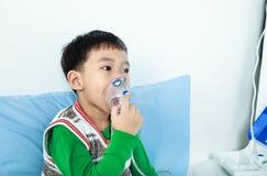 亚裔孩子拿着哮喘的治疗的一台面具蒸气吸入器 免版税库存照片